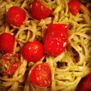 pasta tossed with arugula hazelnut pesto and cherry tomatoes
